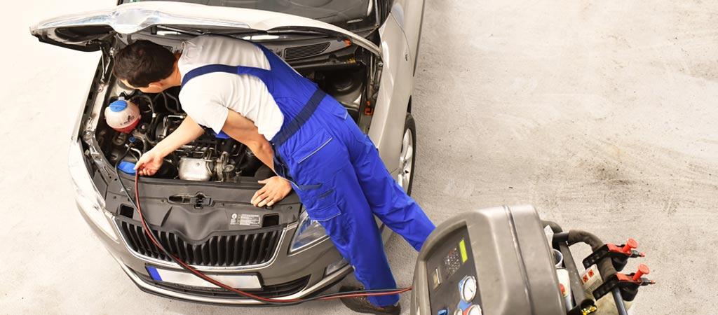 Autmechaniker in einer Werkstatt füllt die Klimaanlage mit Käl